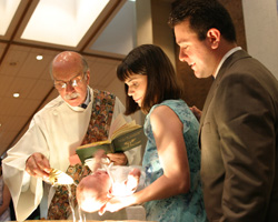 PARENTS PRESENT FOR CHILD'S BAPTISM – Deacon George Reich baptizes Christopher Jack Guarnieri in the presence of parents Patricia and Thomas Guarnieri at St. John Nepomucene Church in Bohemia, N.Y., in 2004. Parents seeking authentically teach the faith to their children can look to the Ten Commandments as a place to help them help their children grow as healthy Christian men and women. (CNS/The Long Island Catholic)