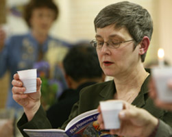 WOMAN PARTICIPATES IN SEDER MEAL – Sandra Steele lifts a cup of grape juice, symbolizing wine, during a Seder meal at St. Thomas More Church in Munster, Ind., March 24. The Seder is a special ritual during the Jewish festival of Passover, a holiday commemorating Jewish deliverance from Egyptian bondage and the time of the barley season. Many Catholics participate in a Seder during the season of Lent. (CNS/Northwest Indiana Catholic)