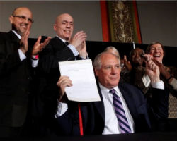 Illinois Governor Pat Quinn holds up the signed civil unions bill