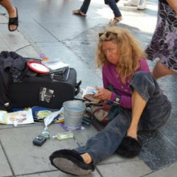 The glamor of tinseltown is tarnished as this homeless woman takes time to rest on Hollywood Boulevard.