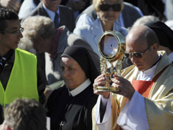 Local priest carries the consecrated host in a procession before about 1000 of the Catholic faithful in Poland