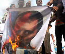 Protesters burn an image of Syrian President Bashar Al-Assad as the rebellion spreads.