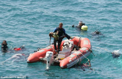 Divers recover the lifeless body of a drowned girl.