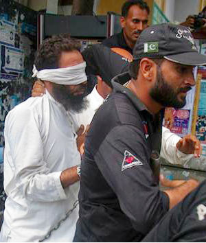 Hafiz Mohammed Khalid Chishti, the cleric in question, pictured here in white, gave police the burned papers as evidence against her. He has been detained since September 1 on suspicion of desecrating the Quran and tampering with evidence.