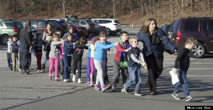 Children with their eyes closed being escorted from their classrooms.