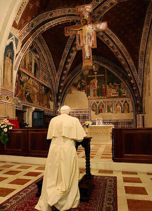 Pope Benedict XVI prays underneath the Saint Damian Crucifix.