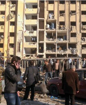 The government and opposition blame each other for two explosions at Aleppo's university on Tuesday, which killed at least 87 people, many of them students attending exams.