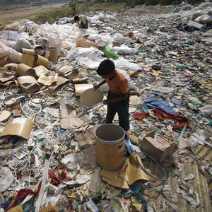 A child walks barefoot atop a water pipe surrounded by a trash-filled cesspool.