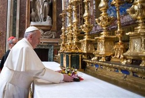 Pope Francis placing flowers at the altar