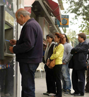 In the Cyprus capital of Nicosia, Cypriots lined up for hours in the hope of withdrawing cash with lines frequently moving at a snail's pace because of the inability of cash machines to dispense more than €40 at a time.