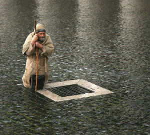 A pilgrim waits in yesterday's rain for the announcement that a new pope has been chosen. The pilgrim represents all of the faithful who wait in prayer.