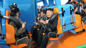 Kim Jong Un prepares to ride a roller coaster, accompanied by his generals.
