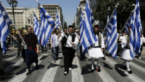 Greek civil servants, dressed in traditional garb, protest pending cuts to their jobs.