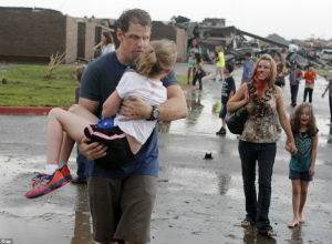 Injured parents walk home after rescuing their children from the destruction at their school where at least 20 other kids perished.