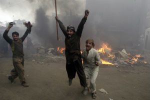 Pakistani men rejoice after burning Christian homes during an anti-Christian riot earlier this year.