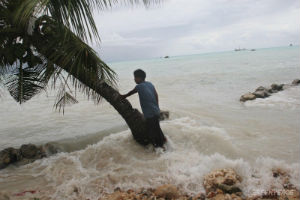 A South Pacific islander watches as a 'king tide' washes over an embankment that used to keep such tides at bay.