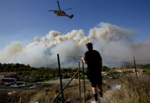 An area resident looks on as helicopters are used to fight the flames.