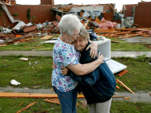 Two friends comfort each other after a tornado devastated their trailer park community this past weekend.
