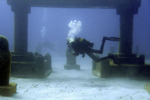 Divers swim through an artificial version of Atlantis in the Caribbean.