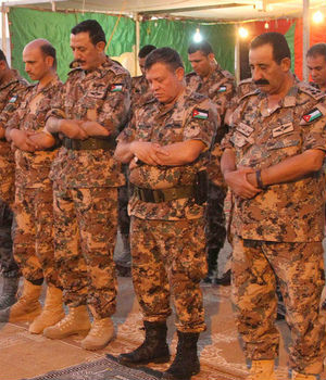 Jordanian troops bow their heads in prayer near the border they share with Syria in August of last year.
