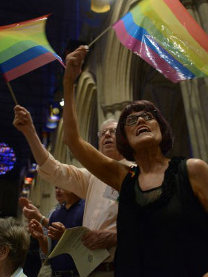 Beth Pattison and husband John Pattison wave rainbow flags during a prayer service for the Lesbian Gay Bisexual Transgender community to mark the Supreme Court's ruling at the National Cathedral on Wednesday, June 26, 2013, in Washington.
