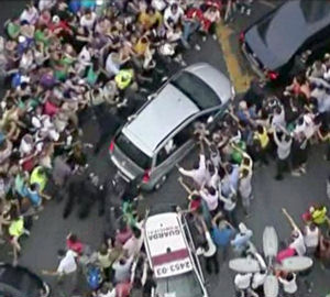 A mob crowds against the Pope's vehicle following his arrival in Rio.