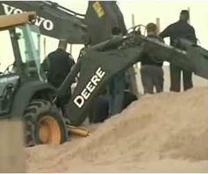 Local police, rescue crews rushed to the scene after the family made a 911 call. Shovels were at first used to move the sand, but the sides of the hole kept collapsing.