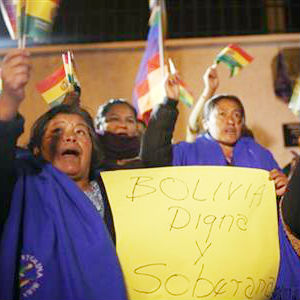 Supporters of Bolivia's President Evo Morales shout slogans and wave Bolivian flags with a sign that reads in Spanish 'Bolivia dignified and sovereign' as they protest outside France's embassy in La Paz, Bolivia,