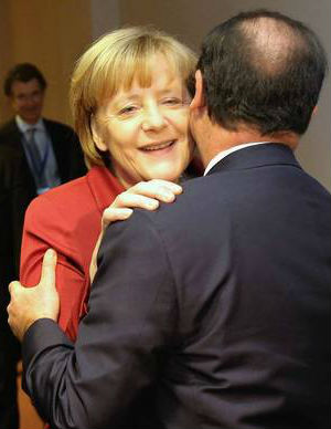 German Chancellor Angela Merkel greets French President Francois Hollande at the European Union summit in Brussels.