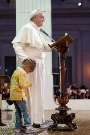 Pope Francis acknowledged the little boy, rubbing his head for a second as the child clings to his side.