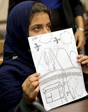 Nine-year-old Nabila held up a hand-drawn picture depicting the strike above her village.