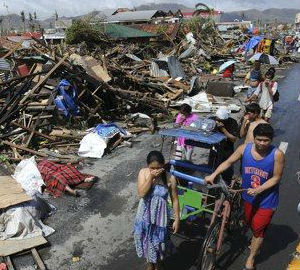 Many survivors in Tacloban merely sit and stare, covering their faces with rags to keep out the smell of rotting corpses.