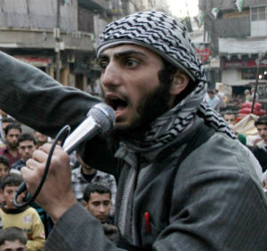 This guy has a pinstripe suit coat on and a pen in his pocket. The new look for anti-government forces in Syria?
