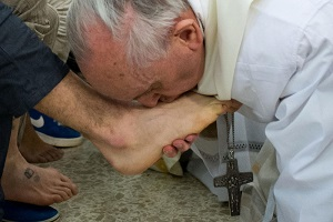Pope Francis kissing the feet of Jesus, as He reveals Himself in the poor
