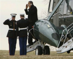 Obama talks on his phone while saluting Marines.
