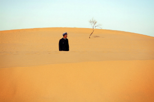 A Chinese man gazes over the sand of an advancing dune.