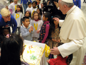 Children helped Pope Francis blow the candles out on his birthday cake.