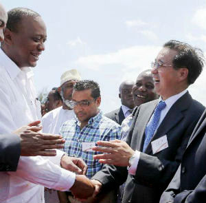 President Uhuru Kenyatta shakes hands with Liu Guangyuan, Chinese ambassador to Kenya upon his arrival during the launching ceremony of a Chinese-funded U.S. 13.8 billion dollar railway project in Mombasa.