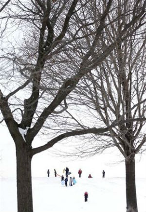 Sledding enthusiasts take to Cricket Hill at Montrose Beach Park in Chicago, despite single-digit temperatures.