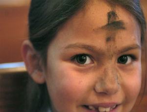 Young boy praying on Ash Wednesday.