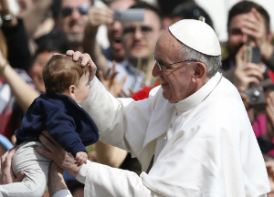 Pope Francis follows the example of St. Joseph, and blesses a child. Our clergy are father figures too.