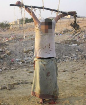 An unidentified man is crucified by Muslim extremists after being accused of spying for the US.