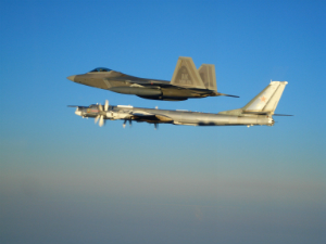 An American F-22 escorts a Tu-95 bomber away from US airspace.