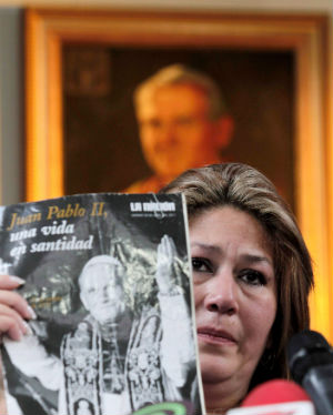 Floribeth Mora Diaz holds up the magazine that laid beside her on her death bed when she prayed to Pope John Paul for a miracle to cure her brain aneurism.