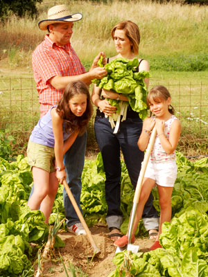 Children woking along parents to grow vegetables for the family.