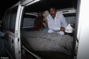 Mohammed Iqbal sits with his wife's body after the police completed their investigation of the scene.