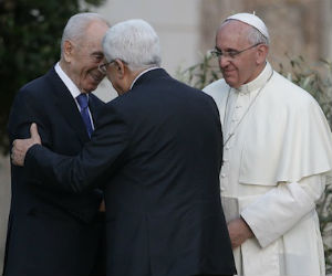 Pope Francis looks on as Shimon Peres and Mahmoud Abbas embrace