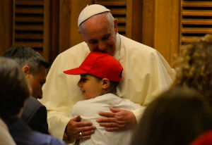 Pope Francis embraces a young student on May 31, 2014 in Paul VI audience hall.