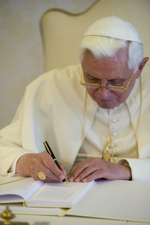 Pope Benedict signs a bound copy of his encyclical.