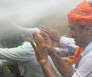 Indian Bharatiya Janata Party (BJP) protesters are hit by water cannon as they stand behind a police barricade during an anti-rape protest in Lucknow.